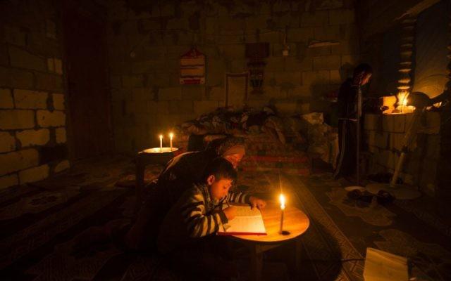 Une Palestinienne aide son fils à faire ses devoirs à la lumière des bougies, alors qu'une crise électrique touche la bande de Gaza, dans le camp de réfugiés de Khan Yunis, le 19 avril 2017. (Crédit : Mahmud Hams/AFP)