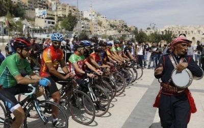 Les cyclistes jordaniens et étrangers regardent un groupe de danseurs traditionnels au théâtre romain antique dans le centre d'Amman lors d'une cérémonie de bienvenue aux participants à la tournée de paix au Moyen-Orient le 24 avril 2017 (Crédit : AFP PHOTO / MENAHEM KAHANA)