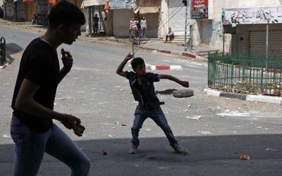 Des manifestants palestiniens jettent des pierres sur des soldats israéliens à Hébron, en Cisjordanie, le 27 avril 2017. Illustration. (Crédit : Hazem Bader/AFP)