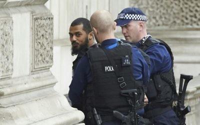 Des officiers britanniques armés ont arrêté un homme en possession de couteau près du Parlement, dans le centre de Londres, le 27 avril 2017. (Crédit : Niklas Halle'n/AFP)