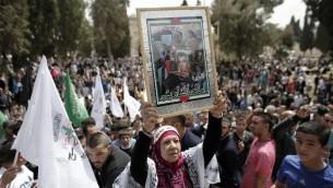 Une femme brandit un portrait d'un prisonnier pendant la journée des prisonniers palestiniens, aux abords du Dôme du Rocher dans le complexe de la mosquée Al-Aqsa, dans la Vieille Ville de Jérusalem, le 17 avril 2015. (Crédit : Ahmad Gharabli/AFP)