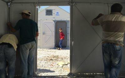 Des hommes assemblent 'Better Shelter', ces refuges temporaires financés par Ikea et utilisés dans les zones touchées par les catastrophes naturelles (Autorisation : Musée d'art de Tel Aviv)