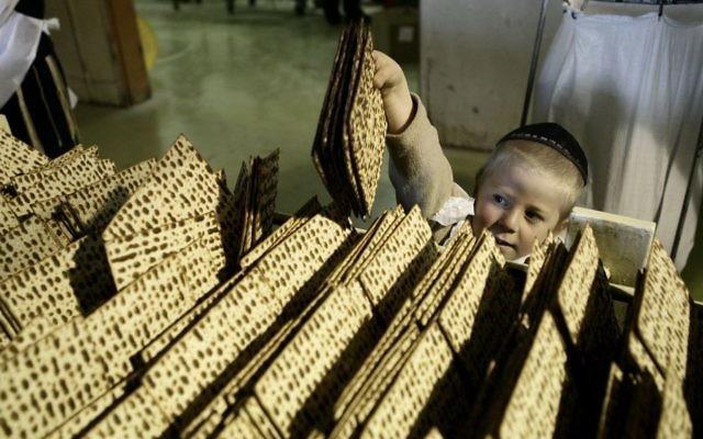 Un enfant entouré de matzas. Illustration. (Crédit : Abir Sultan/Flash90)