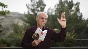 Eli Amir, avec son dernier livre dans sa maison de Jérusalem, en mai 2014. (Crédit : Hadas Parush/Flash90)