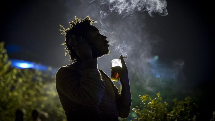 Un artiste fume une cigarette pendant la pause du concert hebdomadaire 'Happy Hour' qui est organisé le jeudi au centre artistique Inema de Kigali, au Rwanda, le 17 février 2017 (Crédit : Miriam Alster/Flash90)