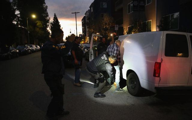 Un homme arrêté par la police des frontières et de l'immigration à  Los Angeles, le 14 octobre 2015 (Crédit : John Moore/Getty Images)