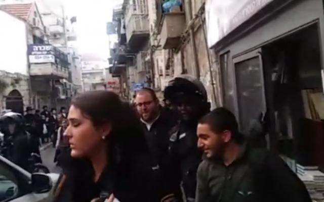 La police a secouru un soldat israélien ultra-orthodoxe qui était piégé dans une librairie par des manifestants ultra-orthodoxes, à Mea Shearim, à Jérusalem, le 2 avril 2017. (Crédit : capture d'écran Kikar HaShabbat)