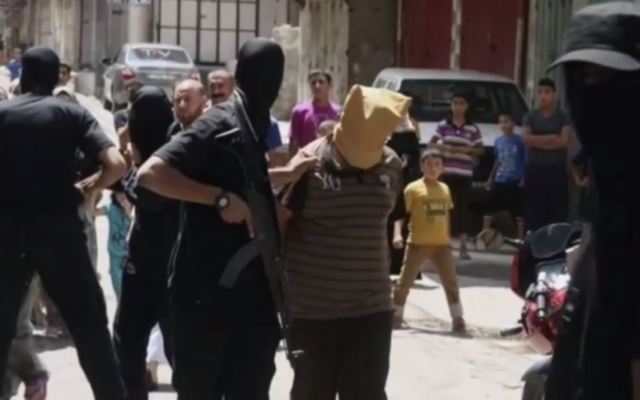 """Un """"collaborateur"""" présumé dans la bande de Gaza, maintenu par un homme armé du Hamas, quelques instants avant son exécution, le 22 août 2014. Illustration. (Crédit : capture d'écran YouTube)"""