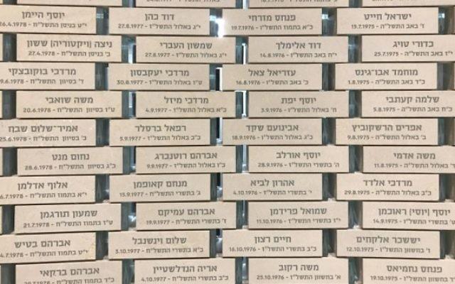 Les briques alignées dans le couloir dans le Hall du Souvenir, chacune portant le nom et la date de la mort d'un soldat tombé aux combats, le 27 avril 2017 (Crédit : Luke Tress / Times of Israel)