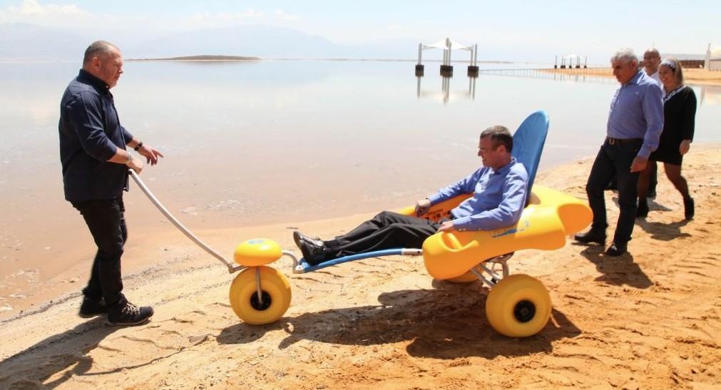 Le chef du conseil régional de Tamar, Dov Litvinoff pousse le ministre du Tourisme Yariv Levin sur une chaise roulante sur la promenade d'Ein Boqek, le 3 avril 3, 2017. La promenadea été conçue avec des facilités d'accès pour les personnes à mobilité réduite. (Crédit : Mickey Lengental)