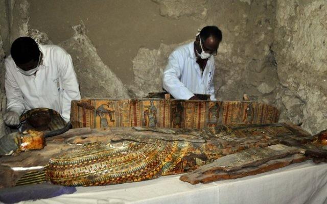 Des archéologues égyptiens travaillent sur un sarcophage en vois découvert dans une tombe de 3 500 ans dans la nécropole de Draa Abul Nagaa, proche de Louxor, en Egypte, le 18 avril 2017. Illustration. (Crédit : AFP/Stringer)