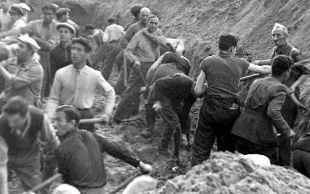 Des Juifs creusent une tranchée dans laquelle ils seront enterrés après avoir été abattus, à Ponary, en Pologne. (Crédit : Yad Vashem)