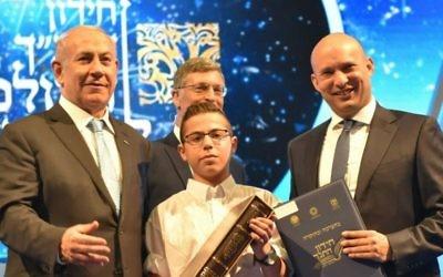 Le Premier ministre Benjamin Netanyahu, à gauche, le ministre de l'Education Naftali Bennett, à droite, et Sagiv Lugasi, vainqueur du Quiz biblique international, à Jérusalem, le 2 mai 2017. (Crédit : Shlomi Amsalem)