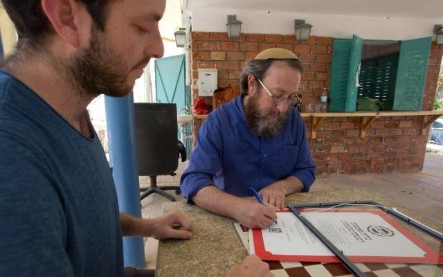 Le rabbin Aaron Leibowitz, au centre, fondateur de Hashgach Pratit (Supervision privée en hébreu), signe un certificat de casheroute alternatif à celui du grand rabbinat pour un bar du centre de Jérusalem, le 8 juin 2016. (Crédit : Menahem Kahana/AFP)