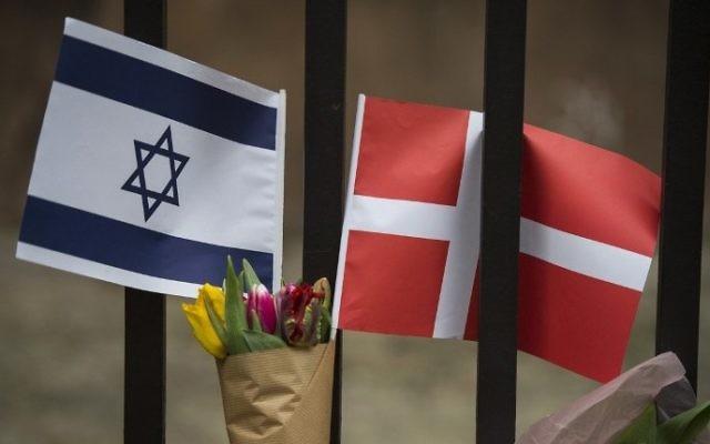 Un drapeau danois et israélien vu parmi les fleurs et les bougies déposés en honneur aux victimes d'une attaque à l'extérieur de la synagogue principale à Copenhague, au Danemark, le 15 février 2015 (Crédit : AFP / Odd Andersen)