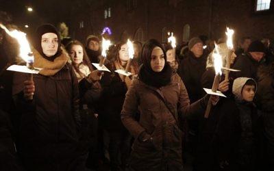 Des gens tiennent des bougies durant un service de commémoration à la mémoire des victimes tuées par un homme armé à Copenhague, le 16 février 2015 (Crédit :: Bax Lindhardt/Scanpix Denmark/AFP)