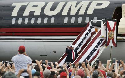 Alors candidat à la présidence, Donald Trump  salue ses partisans avant d'entrer dans son avion après un rassemblement à l'aéroport régional Linder de  Lakeland en Floride, le 12 octobre 2016 (Crédit : Mandel Ngan/AFP)