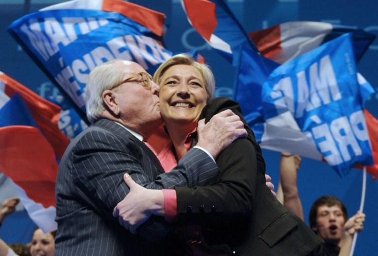 Ce fichier photo pris le 30 mars 2012 montre Marine Le Pen (d) embrassée par son père, président honoraire FN, Jean-Marie Le Pen (g) à la fin d'une réunion de campagne à Nice, dans le sud-est de la France. (Crédit : AFP PHOTO / BORIS HORVAT)