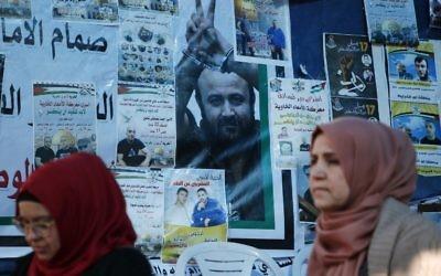 Des Palestiniennes devant un mur d'affiches, dont un portrait de Marwan Barghouthi, pendant un rassemblement de soutien aux prisonniers palestiniens en grève de la faim, à Ramallah, en Cisjordanie, le 24 avril 2017. (Crédit : Abbas Momani/AFP)