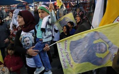 Manifestation de soutien aux prisonniers palestiniens en grève de la faim en Israël, à Ramallah, le 24 avril 2017.  Le drapeau porte un portrait de Marwan Barghouthi. (Crédit : Abbas Momani/AFP)