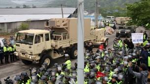 Des manifestants et la police assistent à l'arrivée de camions transportant les équipements de défense contre les missiles THAAD américains sur un site de déploiement à Seongju, le 26 avril 2017 (Crédit : AFP Photo/YONHAP)