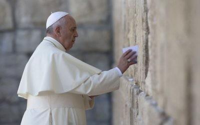Le Pape François place une note  de prière au mur Occidental, le lieu de prière le plus saint du Judaïsme, dans la vieille Ville de Jérusalem le 26 mai 2014 (Crédit  : Thomas Coex/AFP)