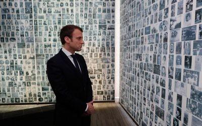 Le candidat français à la présidence pour le mouvement En Marche!,  Emmanuel Macron, regarde les 2500 photographies de jeunes Juifs déportés de France durant l'occupation nazie pendant la Deuxième guerre mondiale au cours d'une visite au mémorial de la Shoah le 30 avril 2017 à Paris  (Crédit : AFP/Pool/Philippe Wojazer)