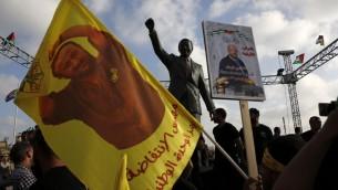 Des manifestants brandissent des portraits de Marwan Barghouthi devant la statue de Nelson Mandela à Ramallah le 3 mai 2017, durant un rassemblement en soutien à Barghouthi et aux autres prisonniers en grève de la faim dans les prisons israéliennes le 24 avril 2017 (Crédit : Abbas Momani/AFP)