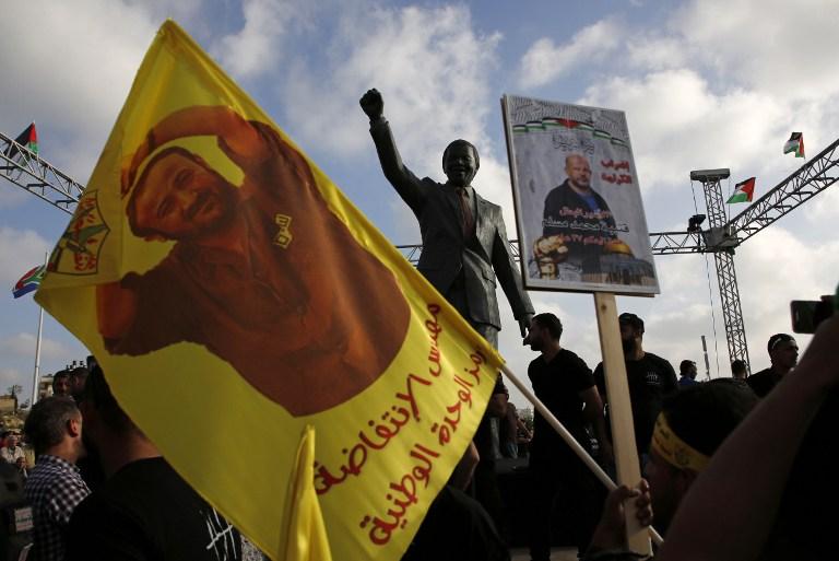 Des manifestants palestiniens brandissent des portraits de Marwan Barghouthi devant la statue de Nelson Mandela pendant un rassemblement de soutien aux prisonniers en grève de la faim dans les prisons israéliennes, à Ramallah, en Cisjordanie, le 3 mai 2017. (Crédit : Abbas Momani/AFP)
