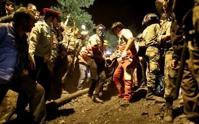 Secouristes sortant un corps d'une mine de charbon qui s'est effondrée à Azad Shahr, dans le nord de l'Iran, après une explosion, le 4 mai 2017. (Crédit : Mostafa Hassanzadeh/Tasnim/AFP)