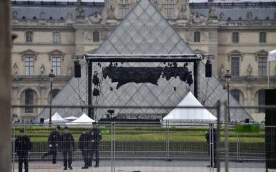 Policiers déployés devant l'esplanade du Louvre après une évacuation en raison d'une alerte de sécurité au jour du second tour de l'élection présidentielle française, le 7 mai 2017. (Crédit : Christophe Archambault/AFP)