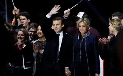 Emmanuel Macron, élu à la présidence de la République française, au centre, et son épouse Brigitte, devant la pyramide du Louvre, le 7 mai 2017. (Crédit : Patrick Kovarik/AFP)