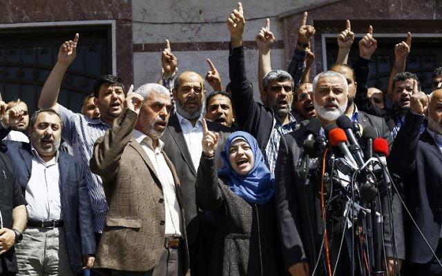Ismail Haniyeh, chef du groupe terroriste du Hamas, annonçant l'arrestation du tueur présumé de Mazen Foqaha, abattu le 24 mars 2017, près de sa maison dans la ville de Gaza, aux côtés de l'épouse de Foqaha et de Yahya Sinwar, chef du Hamas à Gaza, le 11 mai 2017. (Crédit :  Mohammed Abed/AFP)