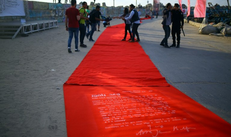 Palestiniens sur le tapis rouge d'un festival de cinéma, sur lequel est inscrit le texte de la déclaration Balfour, à Gaza Ville, le 12 mai 2017. (Crédit : Mohammed Abedi/AFP)