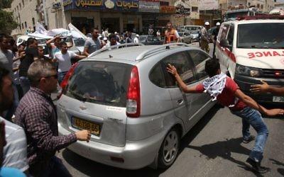 Des manifestants palestiniens encerclent la voiture d'un Israélien qui se fraye un chemin parmi la foule, près du checkpoint d'Hawara, en Cisjordannie, le 18 mai 2017. (Crédit : Jaafar Ashtiyeh/AFP)