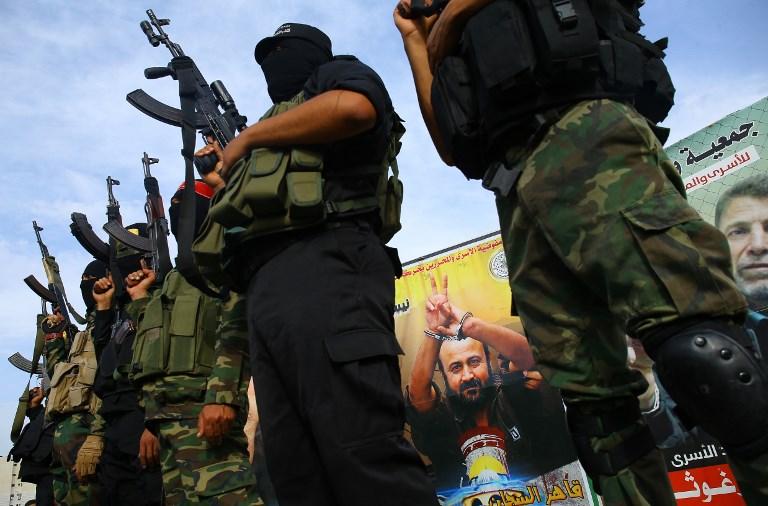 Des membres de groupes terroristes gazaouis devant un portrait de Marwan Barghouthi, pendant une conférence de presse à Gaza Ville en solidarité avec les prisonniers palestiniens en grève de la faim, le 18 mai 2017. (Crédit : Mohammed Abed/AFP)