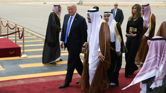 Le président américain Donald Trump, au centre à gauche, est accueilli par le roi saoudien Salman ben Abdel Aziz al-Saoud, au centre, suivis de Melania Trump,  à leur arrivée à l'aéroport international King Khalid de Riyad, le 20 mai 2017. (Crédit : Mandel Ngan/AFP)