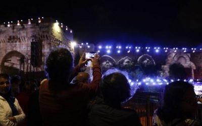 Les gens regardent la photo emblématique prise par David Rubinger de parachutistes israéliens le long du Mur occidental en Juin 1967 au cours d'un spectacle de son et lumière projeté sur les murs de la Vieille ville de Jérusalem pour célébrer le début de la semaine du 50ème anniversaire de la guerre israélo-arabe de 1967, le 20 mai 2017 (Crédit : GALI TIBBON / AFP PHOTO)