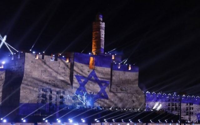 Les gens regardent une projection du drapeau israélien au cours d'un spectacle de son et lumière projeté sur les murs de la Vieille ville de Jérusalem pour célébrer le début de la semaine du 50ème anniversaire de la guerre israélo-arabe de 1967, le 20 mai 2017 (Crédit : GALI TIBBON / AFP PHOTO)