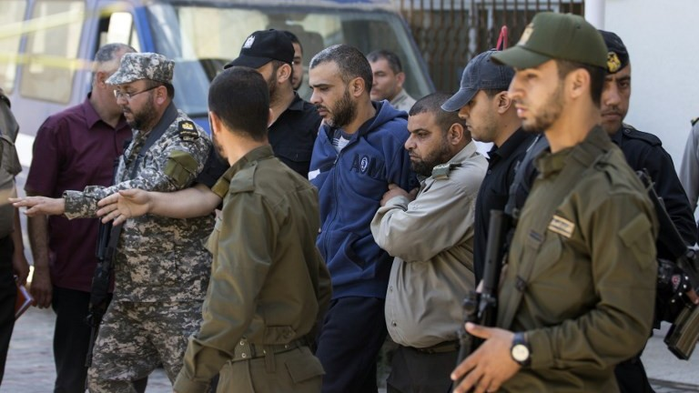 Abdallah al-Nashar, au centre, jugé coupable de complicité de l'assassinat de Mazen Foqaha, escorté par les forces du Hamas devant la cour militaire de Gaza, le 21 mai 2017. (Crédit : Mahmud Hams/AFP)