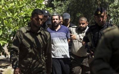 Hisham al-Aloul, au centre, 44 ans, jugé coupable de complicité de l'assassinat de Mazen Foqaha, escorté par les forces du Hamas devant la cour militaire de Gaza, le 21 mai 2017. (Crédit : Mahmud Hams/AFP)