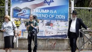 Des israéliens devant un poster qui accueille et soutient le président américain Donald Trump, le 21 mai 2017, en centre ville de Jérusalem, à la veille du séjour de deux jours du président. (Crédit : AFP / Menahem KAHANA)