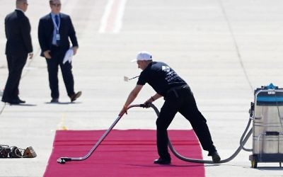 Un employé aspire le tapis rouge que fouleront le président américain Donald Trump et sa femme Melania Trump à l'aéroport international de Ben Gurion, le 22 mai 2017. (Crédit : AFP Photo /Jack Guez)