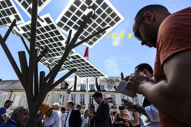 """Le premier """"eTree"""" de France, produit par la start-up franco-israélienne Solar Tree Europ, à son inauguration à Nevers, en France, le 29 mai 2017. (Crédit : Philippe Desmazes/AFP)"""