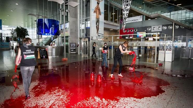 Des membres du mouvement féministe Liliths, ancienne branche des Feman, jettent du faux sang dans les couloirs de l'aéroport de Liège pour protester contre l'opération Bordure protectrice, le 26 août 2014. (Crédit : Nicolas Lambert/Belga/AFP)