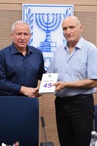 Le médiateur de l'armée israélienne Yitzhak Brick, à droite, donne au parlementaire Avi Dichter une copie de son rapport annuel le 28 mai 2017 (ministère de la Défense)