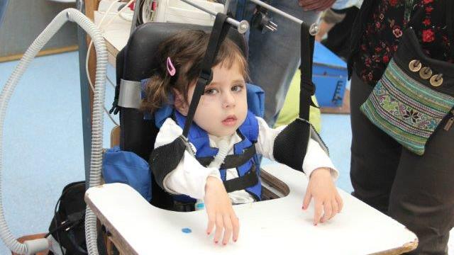 Un enfant utilisant un dispositif de soutien des bras développé à l'ALYN (Autorisation)