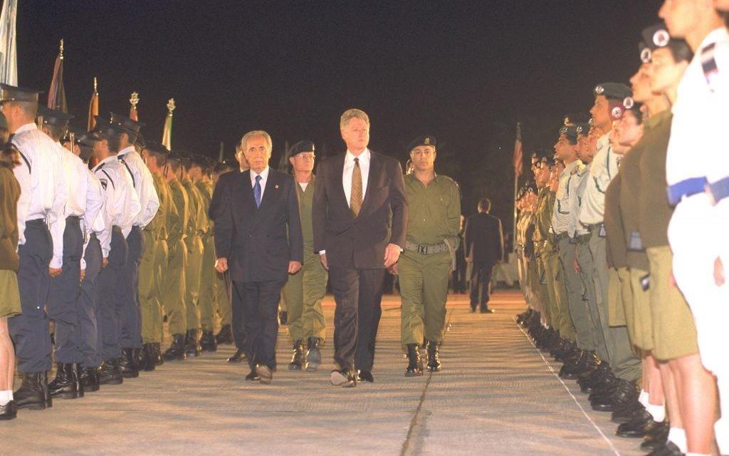 Le président américain Bill Clinton et le Premier ministre Shimon Peres inspectent uen garde d'honneur de l'armée israélienne à l'aéroport Ben Gurion, en mars 1996. (Crédit : Tsvika Israeli/GPO)