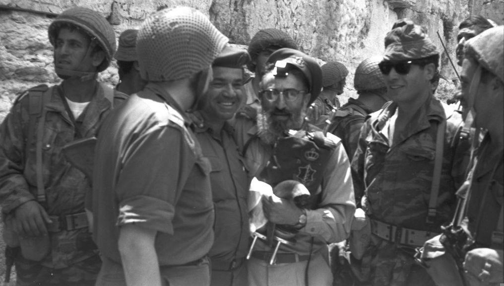Le Grand Rabbin de l'armée Shlomo Goren fabriquant des phylactères et tenant une Torah devant le mur Occidental en 1967. (Crédit : Eli Landau / Government Press Office)
