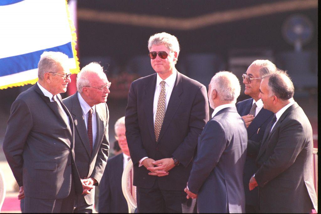 Le président américain Bill Clinton, avec des lunettes de soleil, avec le président Ezer Weizman, le Premier ministre Yitzhak Rabin, et le roi Hussein de Jordanie après la signature du traité de paix israélo-jordanien dans le sédert d'Arava, en octobre 1994. (Crédit : Avi Ohayon/GPO)